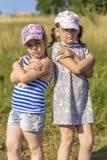 varm sommar Liten flicka som två poserar för kameran fotografering för bildbyråer