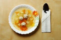 Varm soppa med klimpar på tabellen Arkivfoton