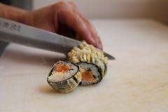 Varm stekt sushirulle: Bitande sushirullar för kniv royaltyfri foto