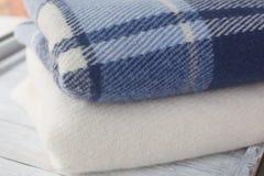 Varm ull filt blått och vitt på fönsterbrädan royaltyfri foto