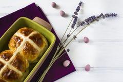 Varma arga bullar för påsk med lavendelblommor, chokladägg på servett och den trävita tabellen Arkivfoto