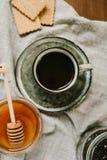 Varma drink och sötsaker Kopp, honung, kex och teblad över t arkivbild