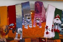 Varma färgrika tumvanten och scarves i en av stallsna på julen marknadsför parkerar in Gorkogo Arkivbild