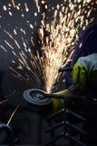 Varma gnistor som flyger, medan arbetaren är det malande stålröret med en cirkelsåg Arkivbilder
