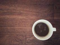 Varma 3 i 1 kaffe med bubblor i den vita koppen på trätabellen royaltyfria bilder