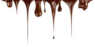 varma isolerade strömmar för choklad drypande Arkivfoto
