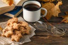 Varma kaffe, tappningbok, exponeringsglas och höstsidor på träbaksida arkivfoton