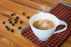 Varma kaffeespresso och kaffebönor på trätabellen royaltyfria foton
