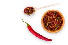 Varma kryddor i en kopp och en sked och en stor chilipeppar Arkivfoton