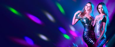 Varma modellflickor som dansar i UV neonljus red f?r diskoflickadeltagare Sexiga unga kvinnor med perfekt slank kroppdans fotografering för bildbyråer