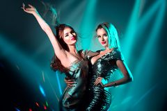 Varma modellflickor som dansar i UV neonljus red f?r diskoflickadeltagare Sexiga unga kvinnor med perfekt slank kroppdans arkivbilder