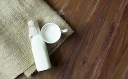 Varma nya mjölkar på träbakgrund Royaltyfria Bilder