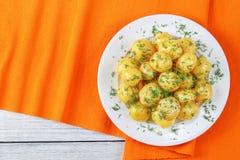 Varma nya potatisar på den vita plattan Arkivfoton