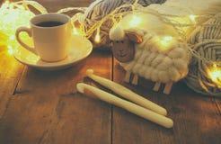 Varma och hemtrevliga garnbollar av ull och den varma koppen kaffe på trätabellen Fotografering för Bildbyråer