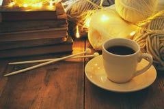 Varma och hemtrevliga garnbollar av ull och den varma koppen kaffe på trätabellen Arkivfoton