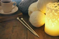 Varma och hemtrevliga garnbollar av ull och den varma koppen kaffe på trätabellen Royaltyfri Fotografi