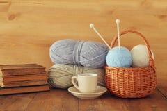 Varma och hemtrevliga garnbollar av ull och den varma koppen kaffe på trätabellen Arkivbild