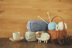 Varma och hemtrevliga garnbollar av ull och den varma koppen kaffe på trätabellen Royaltyfri Foto