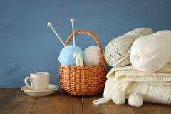 Varma och hemtrevliga garnbollar av ull och den varma koppen kaffe på trätabellen Arkivfoto
