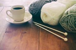 Varma och hemtrevliga garnbollar av ull och den varma koppen kaffe på trätabellen Royaltyfri Bild