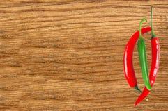 Varma peppar på trätabellslut upp Arkivbild