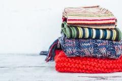 Varma scarves av ljusa färger som ligger i bunt på trätabellen Arkivfoton