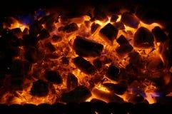 Varma träkol bränner med den ljusa flamman i järnfyrpanna royaltyfri bild