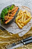 Varmkorv med nötköttkorven och caramelized lökar i en svart bulle Grå färgbakgrund, sidosikt royaltyfria foton