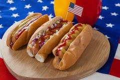 Varmkorv och amerikanska flaggan på den vita trätabellen Royaltyfria Foton
