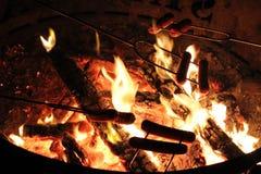 Varmkorvar över campfiren Arkivfoton