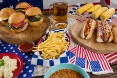 Varmkorvar och hamburgare på trätabellen med 4th det juli temat Arkivfoto