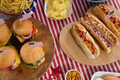 Varmkorvar och hamburgare på trätabellen med 4th det juli temat Royaltyfria Bilder