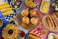 Varmkorvar och hamburgare på trätabellen med 4th det juli temat Arkivbild