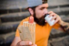 Varmkorvkorv i bulle Skäggig man som äter den sjukliga varmkorvsmörgåsen Hipsteren som dricker kaffe med varmkorven under, vilar royaltyfria foton