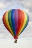 Varmluftsballong som svävar bland moln Arkivbilder