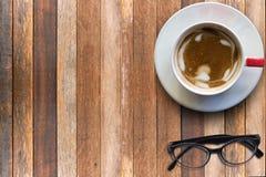 Varmt cappuccino och glasögon på trä Arkivfoto