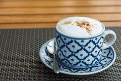 Varmt cappuccinokaffe i kopp på trätabellen arkivbilder