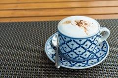 Varmt cappuccinokaffe i kopp p? tr?tabellen royaltyfri foto