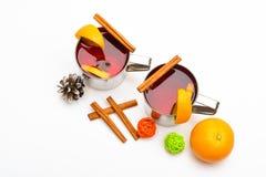 Varmt drinkbegrepp för vinter Rånar med funderat vin eller den varma drinken nära orange frukt på vit bakgrund, slut upp mulled Royaltyfri Bild