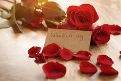 Varmt foto av tre röda rosor med kronblad på den wood tabellen och det pappers- kortet för valentindag Royaltyfri Fotografi