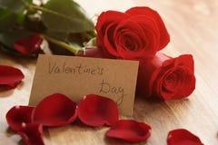 Varmt foto av tre röda rosor med kronblad på den wood tabellen och det pappers- kortet för valentindag Arkivbild