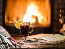 Varmt funderat vin och en bok på trätabellen Arkivbilder