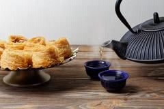 Varmt grönt te hälls in i bunken nära de orientaliska sötsakerna Arkivbild