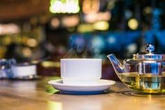 Varmt grönt te i en glass genomskinlig tekanna Royaltyfria Bilder
