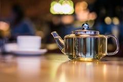 Varmt grönt te i en glass genomskinlig tekanna Arkivfoto