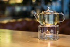 Varmt grönt te i en glass genomskinlig tekanna Arkivfoton