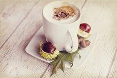 Varmt höstkaffe med skum och kastanjer på en träbackgroun Arkivfoton