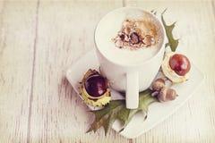 Varmt höstkaffe med skum och kastanjer på en träbackgroun Arkivfoto