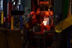 Varmt järn i smeltery rymde vid en arbetare arkivfoton