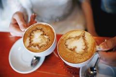 Varmt kaffe i händerna av ett älska par Arkivfoton
